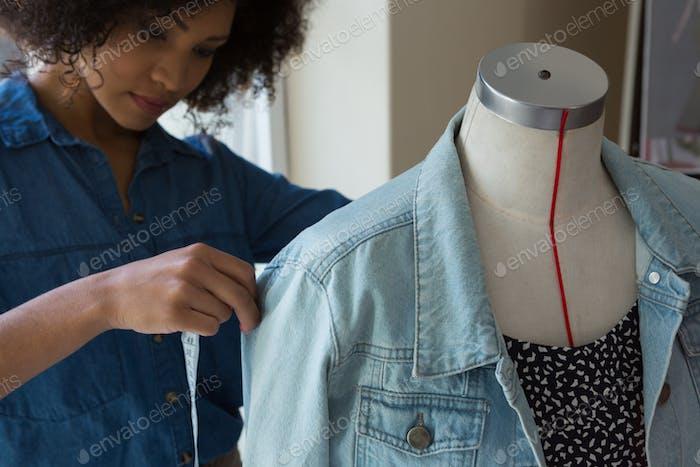 Weibliche Designerin, die die Länge von Denim auf Schaufensterpuppe misst