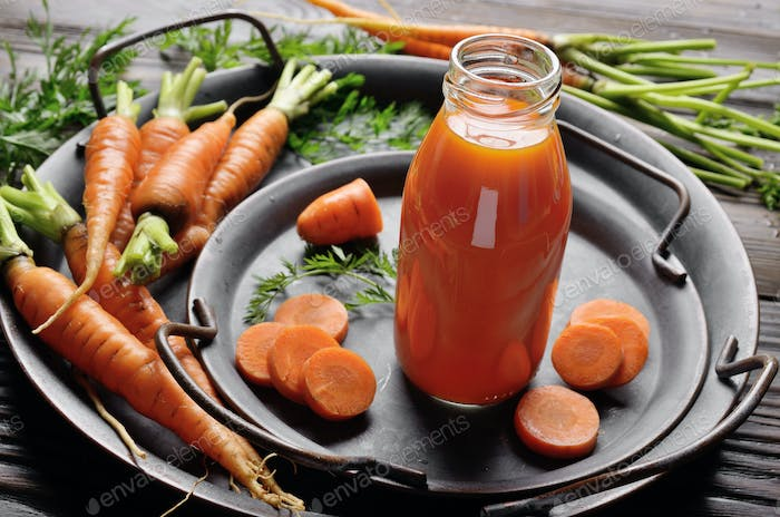 Vegetarian background of old tray with carrots and small bottle