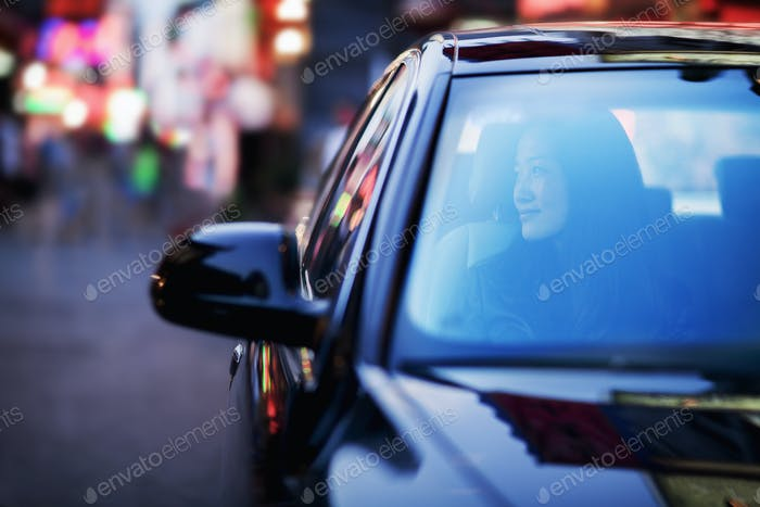 Serene woman looking through car window at the city nightlife