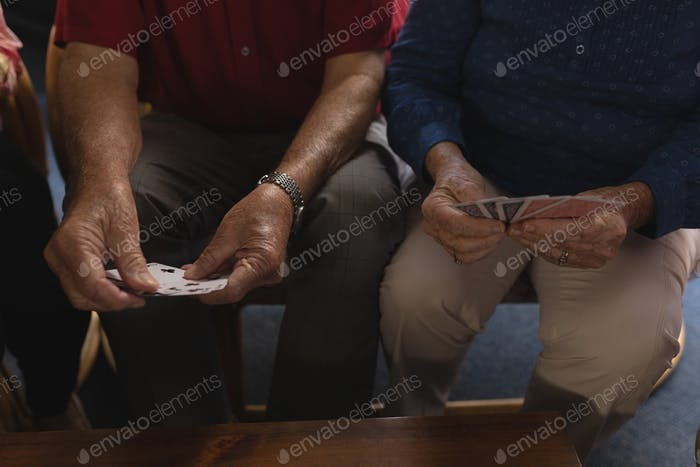 Front view of senior men playing cards at nursing home