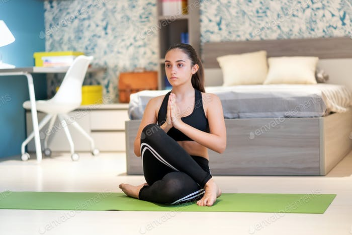 Chica adolescente enfocada practicando asana de yoga en casa