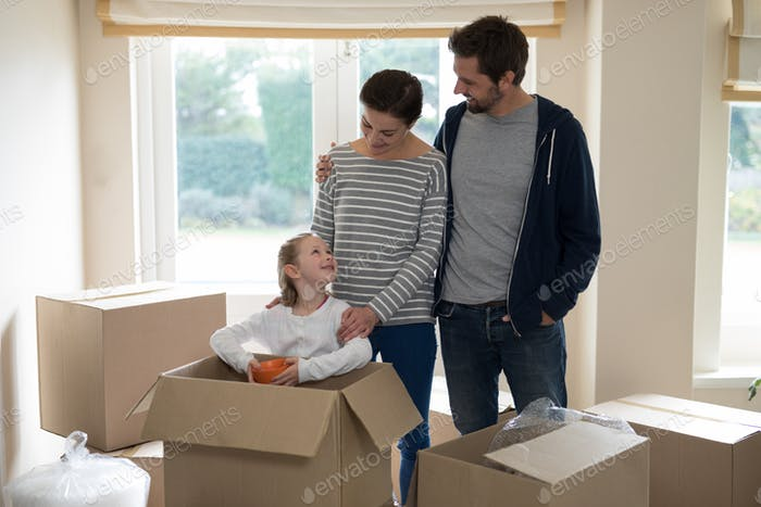 Parents and daughter opening cardboard boxes in living room