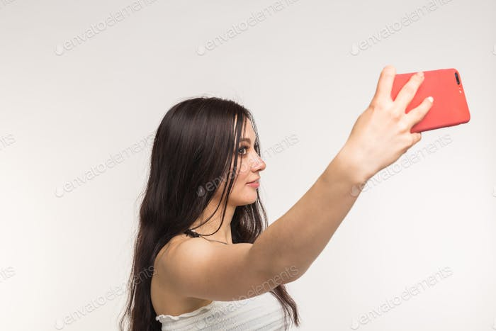 Technology and people concept - young woman making a selfie photo and smiling on white background