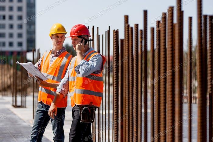 Dos ingenieros estructurales vestidos con camisas, chalecos de Trabajo naranja y cascos exploran la Construcción