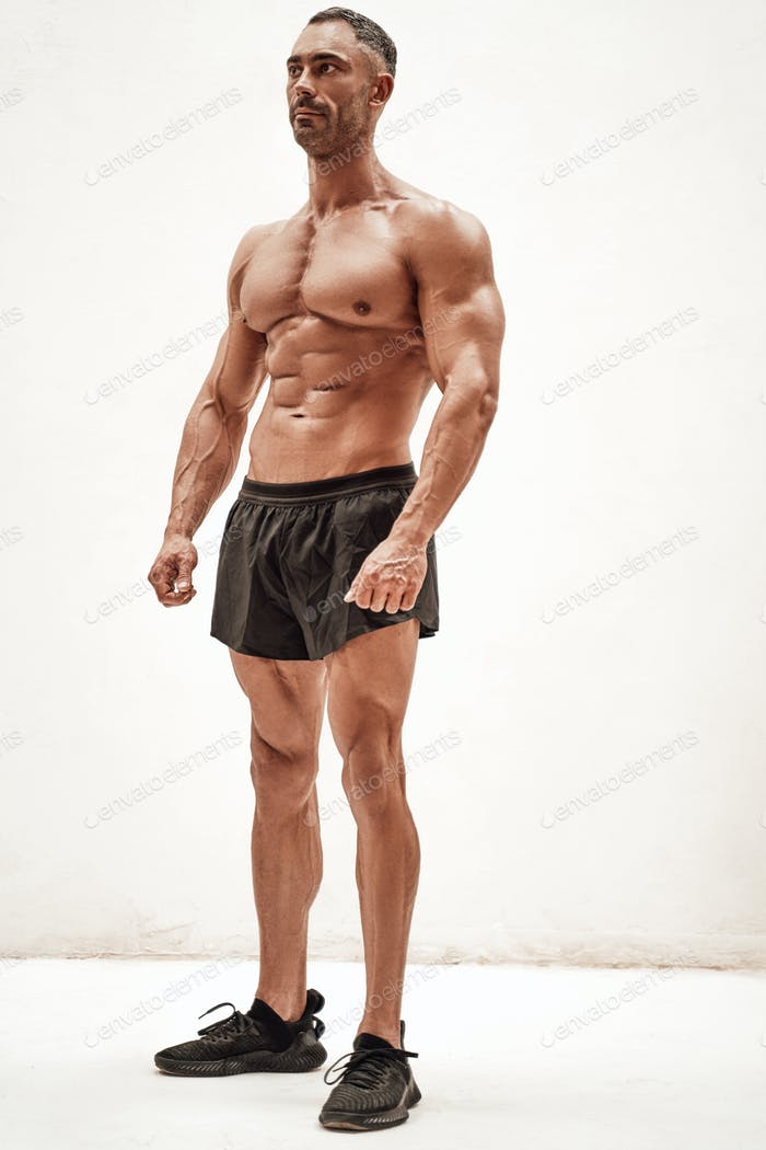 Handsome athlete wearing sportswear posing and looking motivated in a white studio