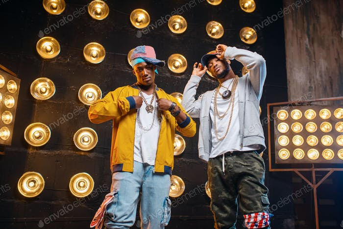 Black rappers in caps on stage with spotlights