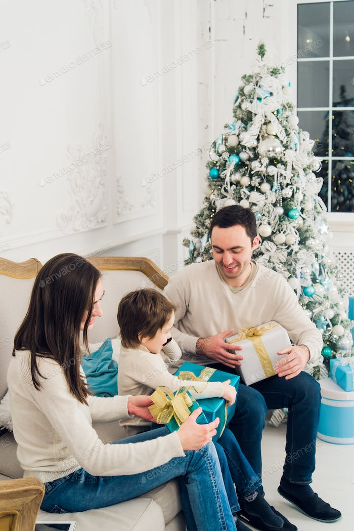 happiness, generation, holidays and people concept - happy family with gift boxes sitting on couch
