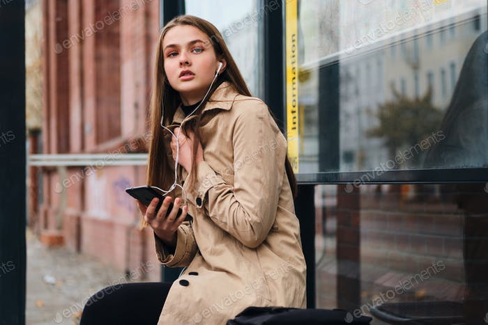 Attractive casual girl in earphones with cellphone thoughtfully waiting public transport on bus stop