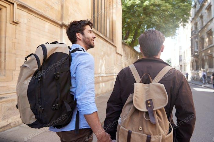 Rückansicht der männlichen Homosexuell Paar im Urlaub tragen Rucksäcke halten Hände Walking entlang City Street