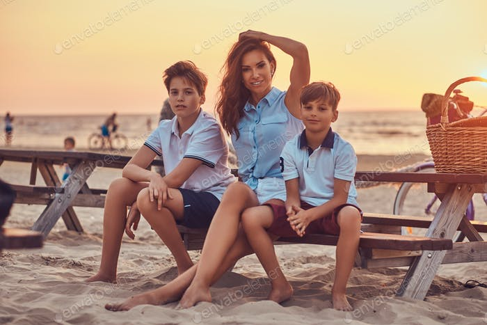 Happy family sitting on a bench against the background of a seacoast at the bright sunset.