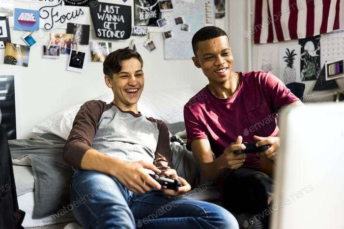Teenage boys hanging out in a bedroom playing video games together