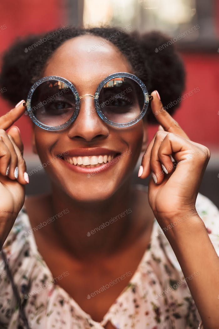 Portrait of cheerful african girl with dark curly hair in sungla