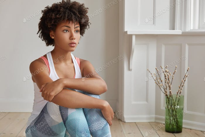 Shot of thoughtful carefree woman with Afro haircut, dressed in sportsclothes, focused into distance