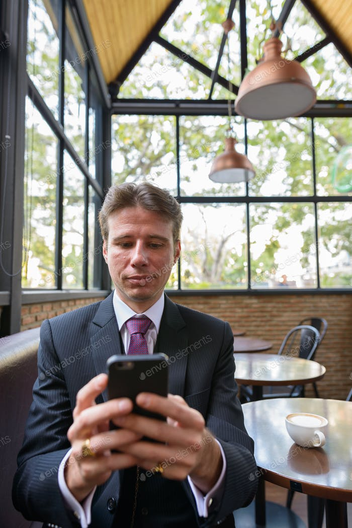 Businessman using mobile phone in coffee shop