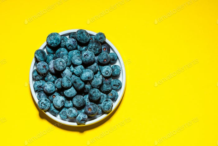 Market Fresh Blueberry on Vibrant Yellow Background. Food Background with Copy Space