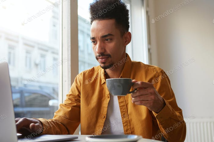Portrait of young attractive African American boy, works at a laptop in a cafe