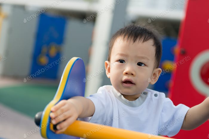 Little toddler Asian boy having fun on playground