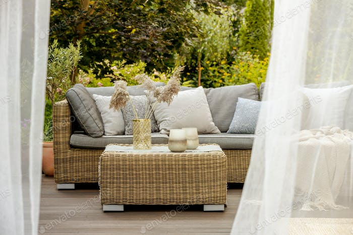 Lanterns, candles and vases on wicker coffee table in front of garden sofa