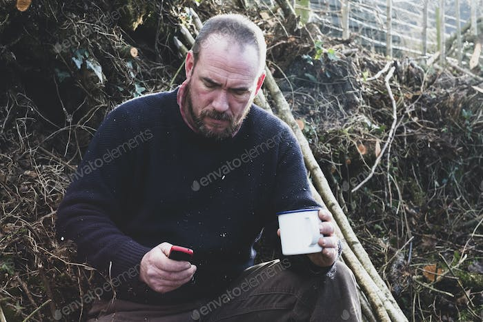Bearded man sitting on ground next to bunch of wooden stakes, holding mug, checking his mobile