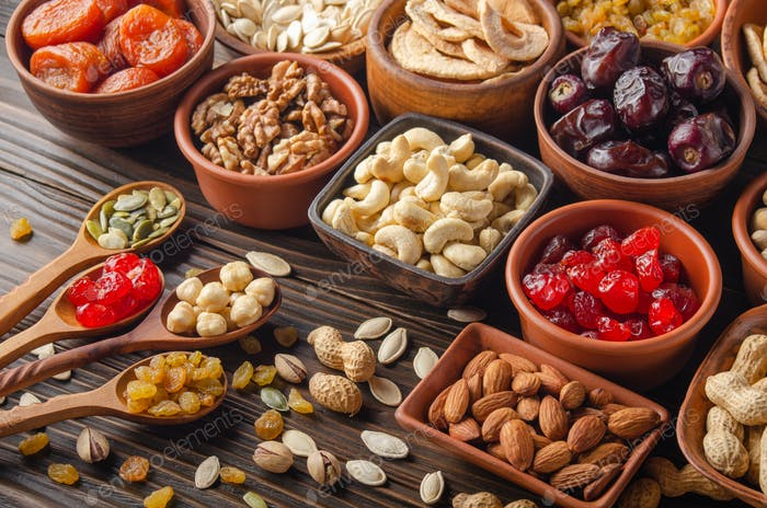Different nuts seeds and dried fruits in bowls and spoons on wooden kitchen table