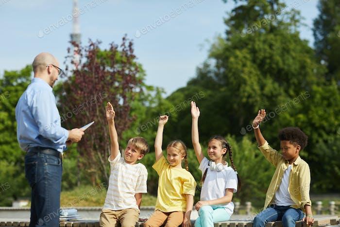 Gruppe von Kindern, die Hände in Outdoor-Unterricht heben