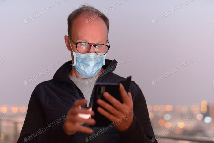 Mature man with mask using phone against view of the city