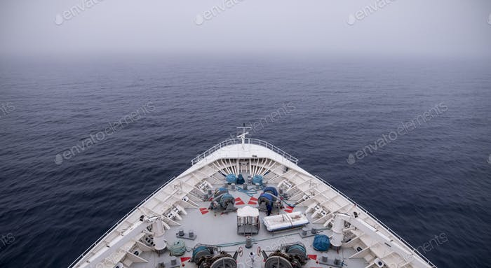 Bow of ship moving through heavy fog, with motion blur on waves.