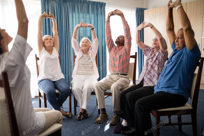Seniors stretching with female doctor while sitting on chairs