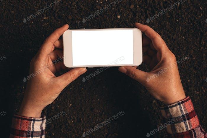 Farmer halten leere Bildschirm Handy über Boden Boden