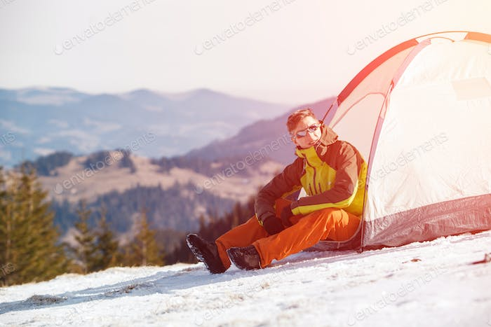 Hiker in tent on mountainside.