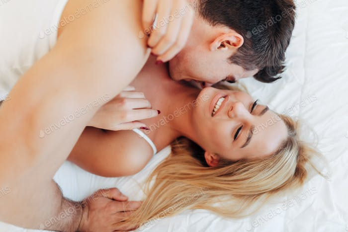 Tenderness od a beautiful couple in bedroom