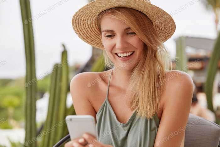 Pleased smiling young female with cheerful expression wears summer clothing, happy to recieve messag