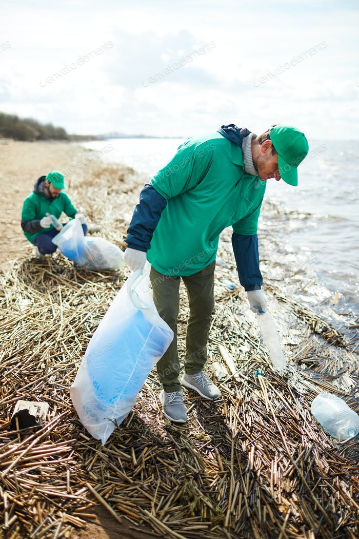 Picking up litter by waterside