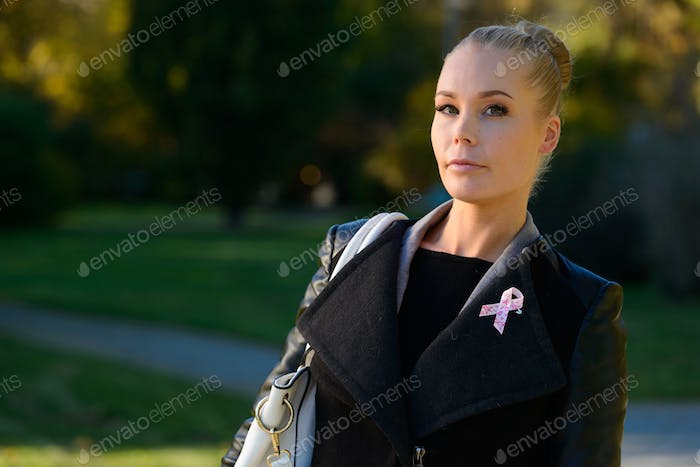 Young beautiful woman standing while wearing pink ribbon for symbol of breast cancer awareness