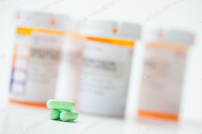 Grüne Kapseln vor orangefarbenen Apothekenflaschen