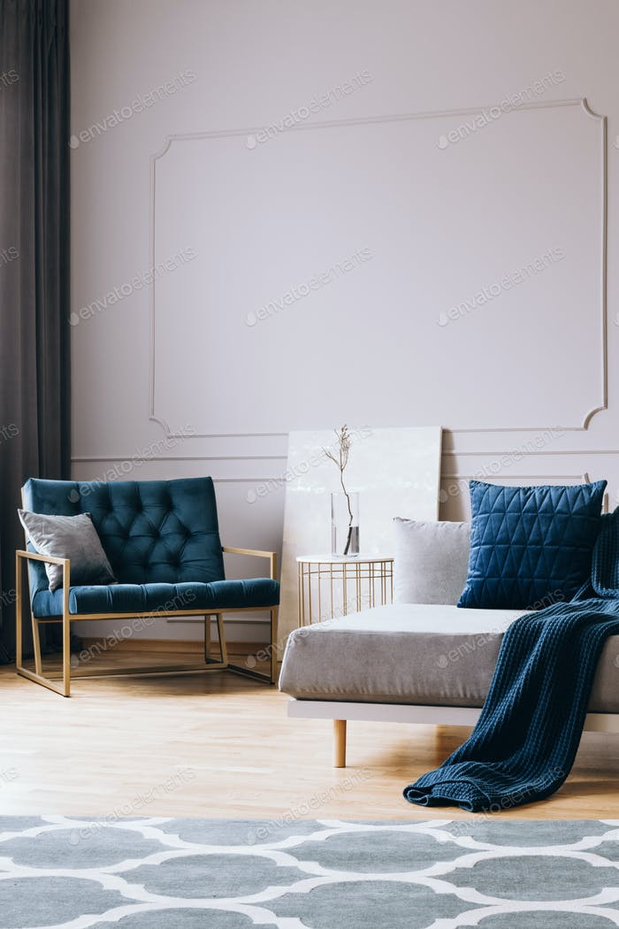 Petrol blue velvet armchair in stylish living room interior in trendy apartment
