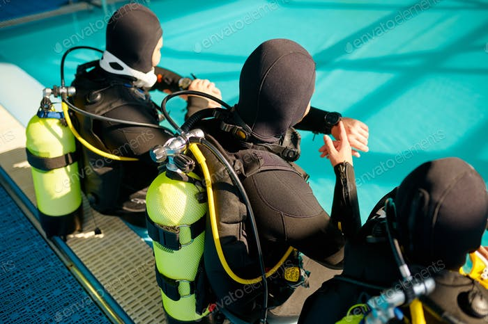 Divemaster and two divers preparing for the dive