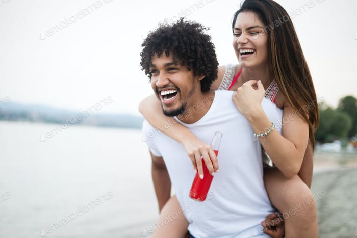 Smiling happy couple having fun on the beach. Holidays, vacation, love and friendship concept
