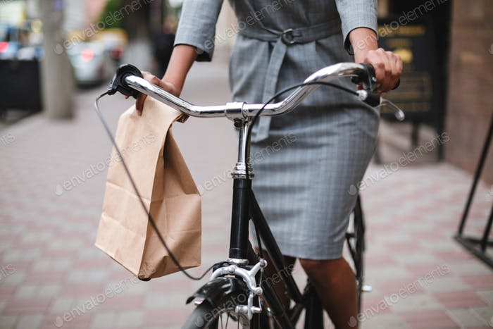 Close up photo of woman body in gray dress riding on bicycle along the street