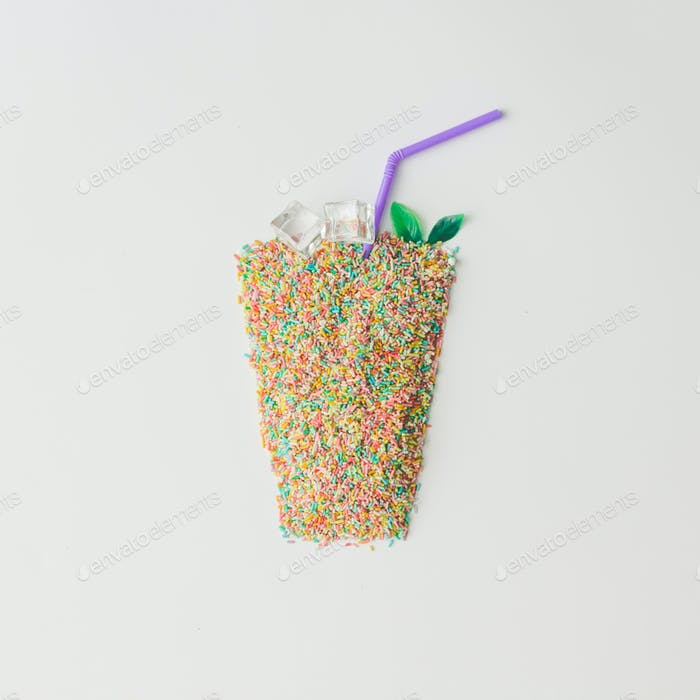 Juice glass made of colorful cake sprinkles with ice cubes. Creative minimal drink concept.