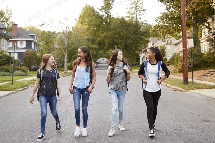 Four young teen girls walking in the road, full length
