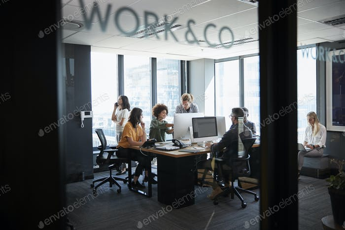 Creative business team working in a casual office, seen through glass wall with text on it