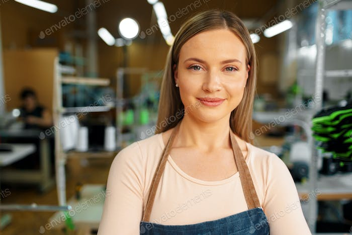 Portrait of a seamstress standing at working place and looking at camera