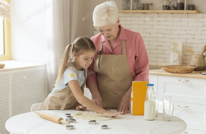 Happy granny with grandchild cutting cookies from dough at home