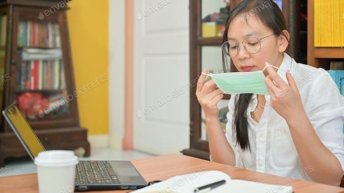 Asiatische Frau trägt eine Maske. Sie arbeitet zu Hause, um gegen Corona-Virus oder Covid-19 zu schützen.