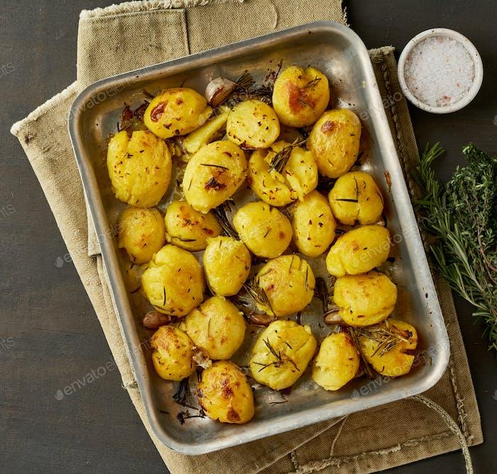 Ofen gebacken ganze zerkleinerte und knusprige Kartoffelspuds mit Gewürzen und Kräutern in Metallic-Tablett.