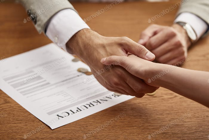 partial view of man and woman shaking hands near bankruptcy form