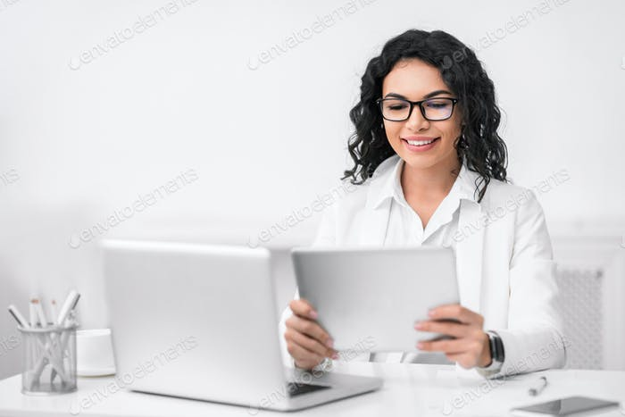 Portrait of busy hispanic girl using tablet and computer