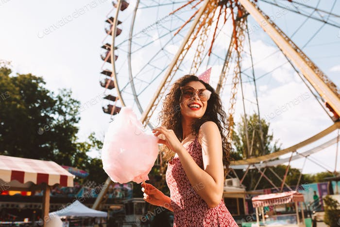 Happy girl in sunglasses and birthday cap eating cotton candy in amusement park over ferris wheel
