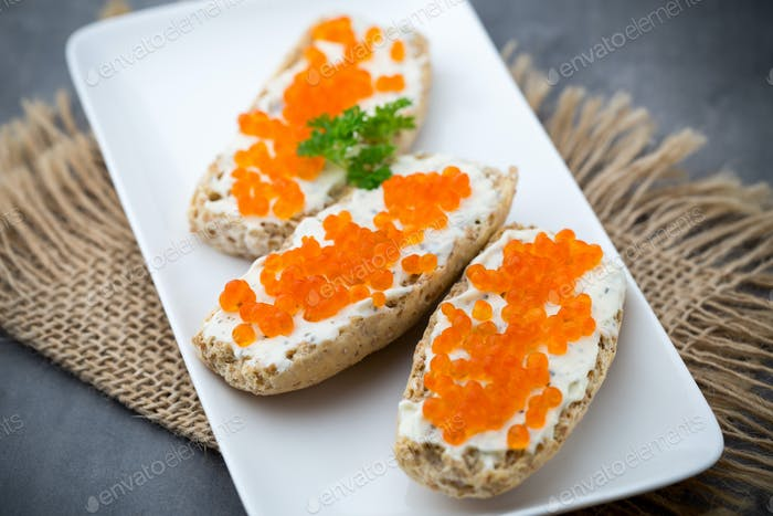 Red caviar on bread on white plate.